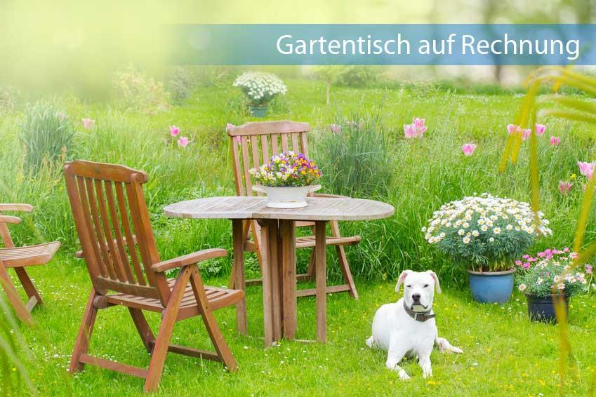 Hölzerner Gartentisch auf Rechnung in grün blühenden Garten